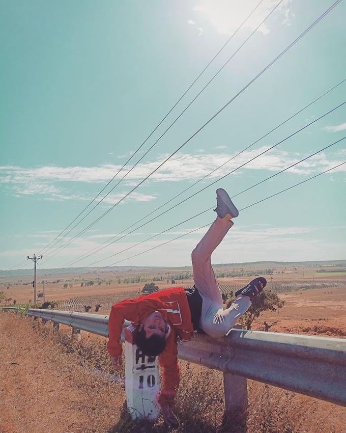 """Trên đường đi sa mạc Hòa Thắng, Nghĩa cũng không quên làm một kiểu té xỉu bên lề đường vì """"cảnh quê mình đẹp quá"""". Đây là đoạn đường mà chỉ có người địa phương hoặc dân ưa du lịch khám phá biết. Nó giao với đường ven biển mà bạn phải để ý thật kỹ mới không bị lỡ."""